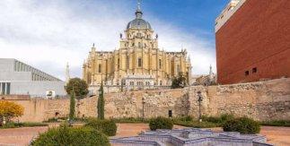 Visita Madrid de las tres culturas: cristianos, judíos, musulmanes y su integración social. Restos de la muralla árabe con el Museo de Colecciones Reales y la Catedral de la Almudena al fondo